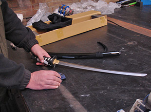 A photo of a sword being prepared for despatch